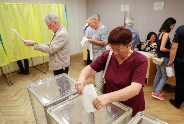A voter casts her ballot at a polling station during a parliamentary election in Kiev, Ukraine July 21, 2019. REUTERS/Gleb Garanich