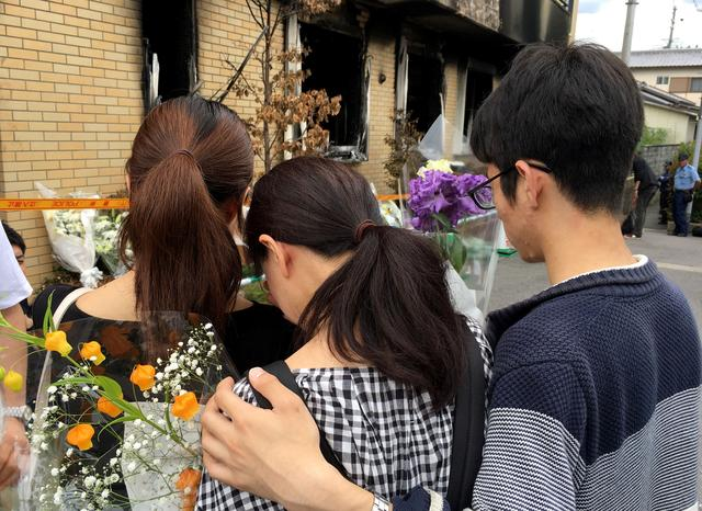 People react as they visit the Kyoto Animation building which was torched in an arson attack, in Kyoto, Japan, July 21, 2019. REUTERS/Tim Kelly