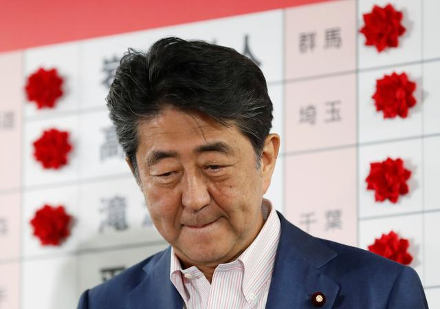 Japan's Prime Minister Shinzo Abe, who is also leader of the ruling Liberal Democratic Party (LDP), looks on as he puts a rosette on the name of a candidate who is expected to win the upper house election, at the LDP headquarters in Tokyo, Japan, July 21, 2019. REUTERS/Kim Kyung-Hoon