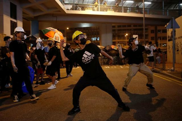 An anti-extradition demonstrator throws an egg at a police station, after a march to call for democratic reforms in Hong Kong, China July 21, 2019. REUTERS/Edgar Su