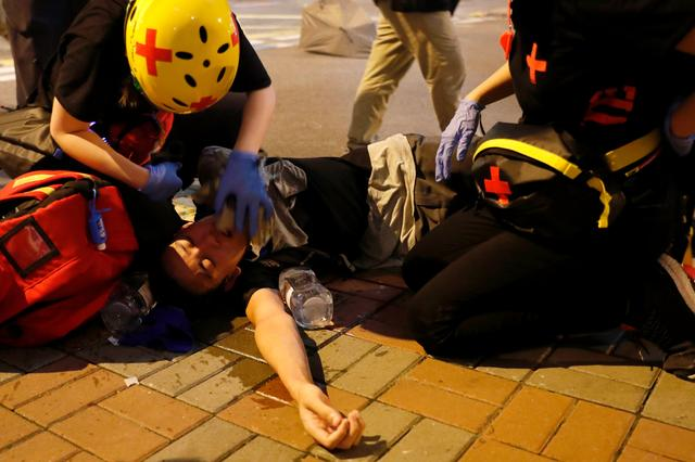 An anti-extradition bill demonstrator receives medical attention after riot police fire tear gas after a march to call for democratic reforms, in Hong Kong, China July 21, 2019. REUTERS/Tyrone Siu