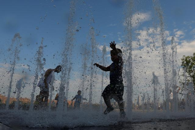Children play in a water feature in Domino Park as a heatwave continued to affect the region in Brooklyn, New York City, New York, U.S., July 21, 2019. REUTERS/Andrew Kelly