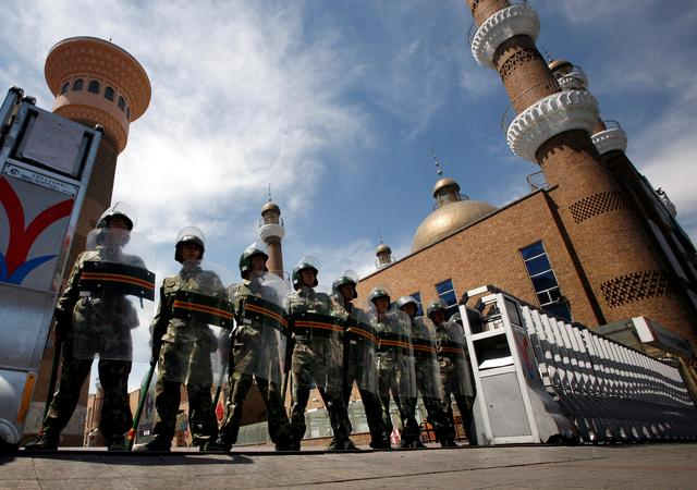 FILE PHOTO: Chinese paramilitary police in riot gear stand guard across the entrance to a large mosque in the centre of the city of Urumqi in China's Xinjiang Autonomous Region July 9, 2009.  REUTERS/David Gray/File Photo