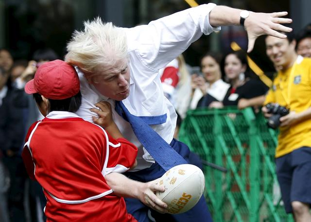 FILE PHOTO: London's Mayor Boris Johnson collides with 10-year-old Toki Sekiguchi during a game of Street Rugby with a group of Tokyo children, outside the Tokyo Square Gardens building October 15, 2015. REUTERS/Issei Kato/File Photo