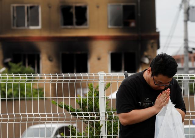 A man prays for victims in front of the torched Kyoto Animation building in Kyoto, Japan, July 20, 2019. REUTERS/Kim Kyung-Hoon