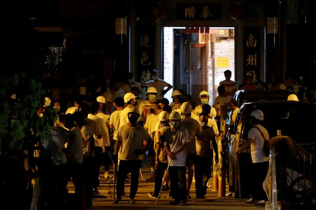 Men in white T-shirts and carrying poles are seen in Yuen Long after attacking anti-extradition bill demonstrators at a train station in Hong Kong, China, July 22, 2019. REUTERS/Tyrone Siu