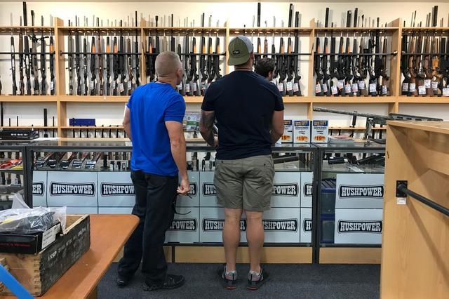 FILE PHOTO: People look at firearms and accessories on display at Gun City gunshop in Christchurch, New Zealand, March 19, 2019. REUTERS/Jorge Silva/File Photo