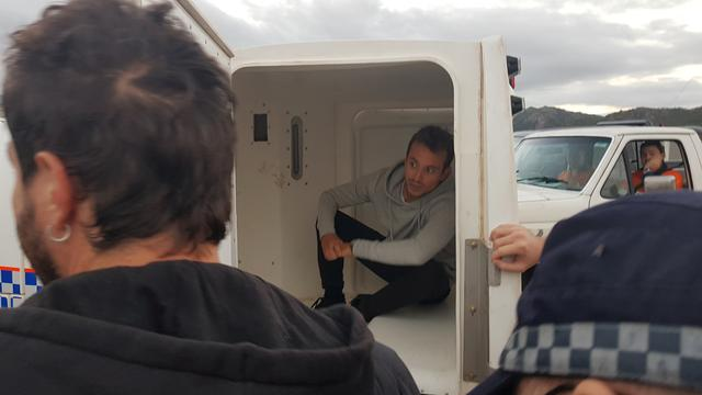 French TV reporter Hugo Clement is seen in a police van after he was arrested while filming protesters blockading the Abbot Point coal port near Bowen, Queensland, Australia July 22, 2019. Frontline Action on Coal/Handout via REUTERS