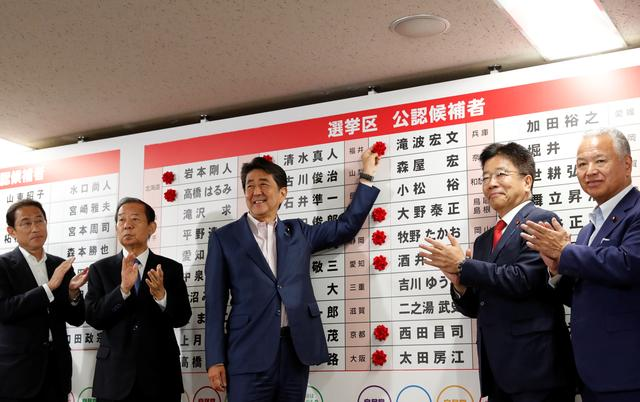 Japan's Prime Minister Shinzo Abe, who is also leader of the ruling Liberal Democratic Party (LDP), puts a rosette on the name of a candidate who is expected to win the upper house election, at the LDP headquarters in Tokyo, Japan, July 21, 2019. REUTERS/Kim Kyung-Hoon