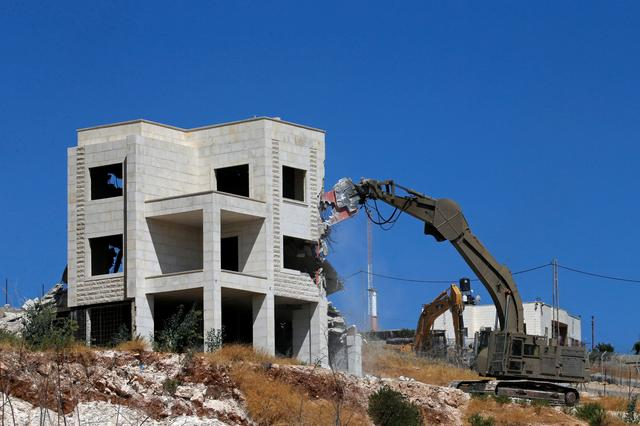An Israeli machinery demolishes a Palestinian house in the village of Sur Baher which sits on either side of the Israeli barrier in East Jerusalem and the Israeli-occupied West Bank July 22, 2019. REUTERS/Mussa Qawasma