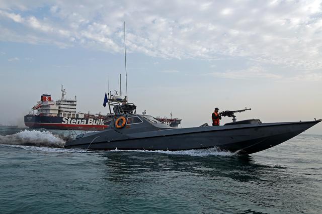 A boat of the Iranian Revolutionary Guard sails next to Stena Impero, a British-flagged vessel owned by Stena Bulk, at Bandar Abbas port, July 21, 2019. Iran, Mizan News Agency/WANA Handout via REUTERS