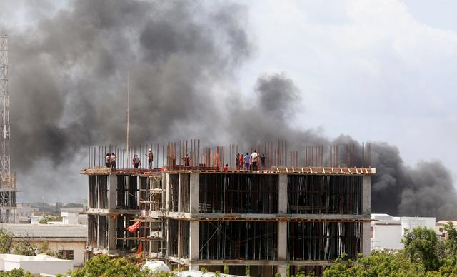 Workers are seen on a construction site as smoke billows from the scene of an explosion in Mogadishu, Somalia July 22, 2019. REUTERS/Feisal Omar