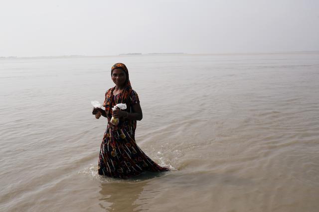 A flood-affected woman wades through flooded area in Jamalpur, Bangladesh July 21, 2019. REUTERS/Mohammad Ponir Hossain