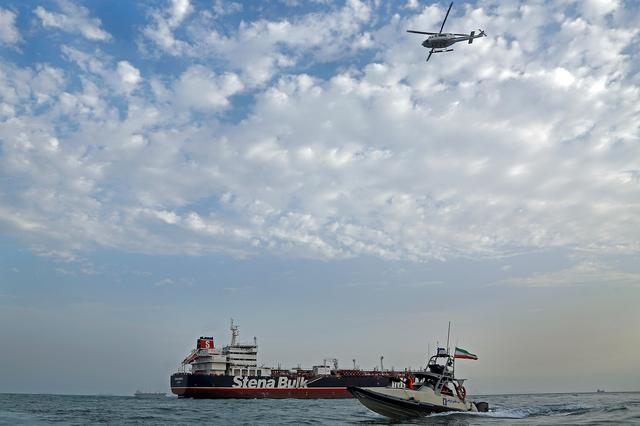FILE PHOTO - A boat of the Iranian Revolutionary Guard sails next to Stena Impero, a British-flagged vessel owned by Stena Bulk, at Bandar Abbas port, July 21, 2019. Picture taken July 21, 2019. Iran, Mizan News Agency/WANA Handout via REUTERS
