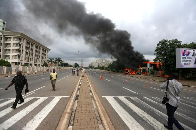 A police officer walks past a photographer after the Shi'ite group set an ambulance and a fire engine on fire at the Federal Secretariat in Abuja, Nigeria July 22, 2019. REUTERS/Afolabi Sotunde