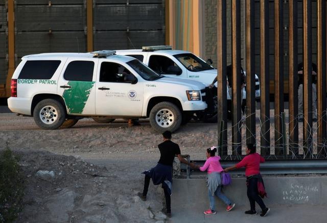 Foto de archivo. Una familia de migrantes camina a través del muro que divide México de Estados Unidos para entregarse a autoridades estadounidenses en El Paso, Texas, visto desde Ciudad Juárez, México. 9 de julio 2019. REUTERS/Daniel Becerril
