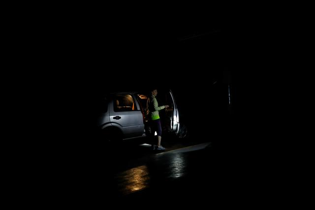 A man uses a flashlight to illuminate a woman boarding her car at a parking garage during a blackout in Caracas, Venezuela July 22, 2019. REUTERS/Carlos Garcia Rawlins