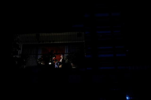 Una mujer sentada en un balcón de un apartamento durante el apagón en Caracas, Venezuela 22 de julio de 2019. REUTERS/Carlos Garcia Rawlins
