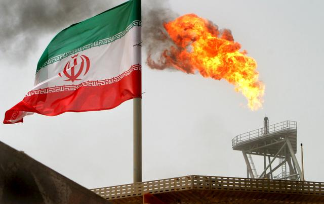 FILE PHOTO: A gas flare on an oil production platform in the Soroush oil fields is seen alongside an Iranian flag in the Gulf July 25, 2005. REUTERS/Raheb Homavandi/File Photo