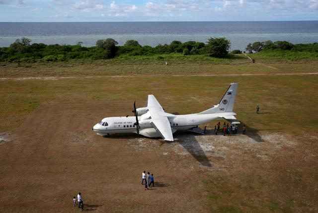 FILE PHOTO: People walk towards a parked Philippine Air Force plane in Philippine occupied Thitu Island in the Spratly Islands in the disputed South China Sea, April 21, 2017. REUTERS/Erik De Castro/File Photo