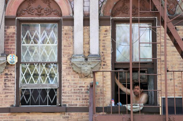 A man peers from a Lower East Side apartment window as a heatwave continued to affect the region in Manhattan, New York City, New York, U.S., July 21, 2019. REUTERS/Andrew Kelly