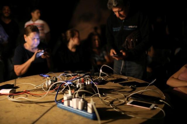 Residentes de Caracas cargan sus teléfonos celulares gracias a un generador eléctrico facilitado por las autoridades durante un nuevo apagón. 22 julio 2019. REUTERS/Manaure Quintero