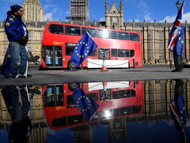 FILE PHOTO: Anti-Brexit demonstrators waving EU and Union flags are reflected in a puddle in front of the Houses of Parliament in London, Britain, March 28, 2018. REUTERS/Toby Melville/File Photo