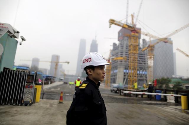 FOTO DE ARCHIVO. Un empleado observa la entrada de un sitio de construcción en un distrito del centro de Pekín. REUTERS/Jason Lee