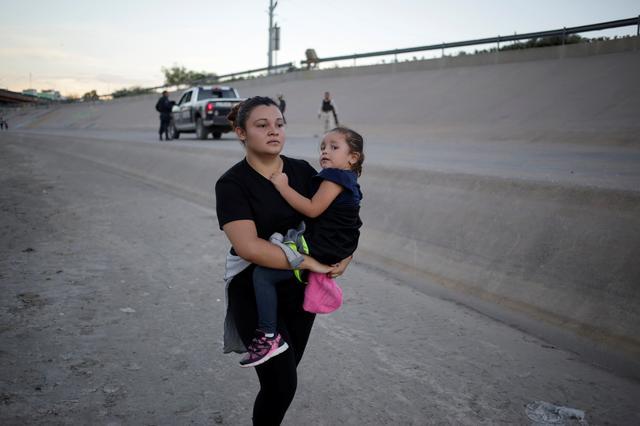 Una mujer inmigrante con su hija en brazos se aleja de efectivos de la Guardia Nacional Mexicana cerca del Río Bravo.  Ciudad Juárez, Mexico. Julio 20, 2019. REUTERS/Daniel Becerril.