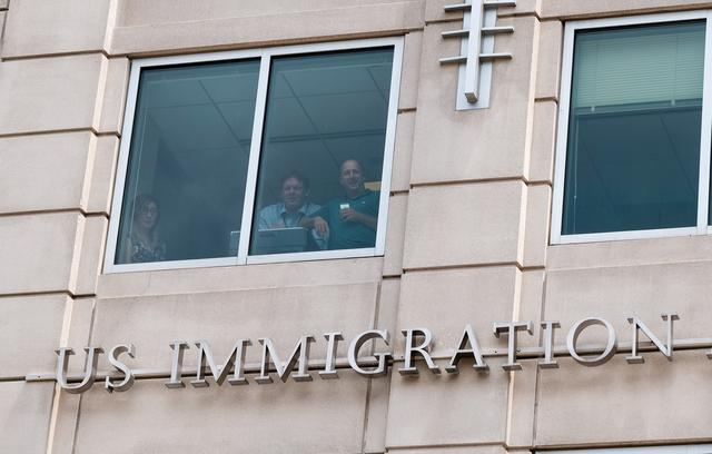 "FILE PHOTO: U.S. Immigration and Customs Enforcement employees watch from a window as activists hold the ""Shutdown ICE"" rally in Washington, U.S., July 16, 2019. REUTERS/Michael A. McCoy"
