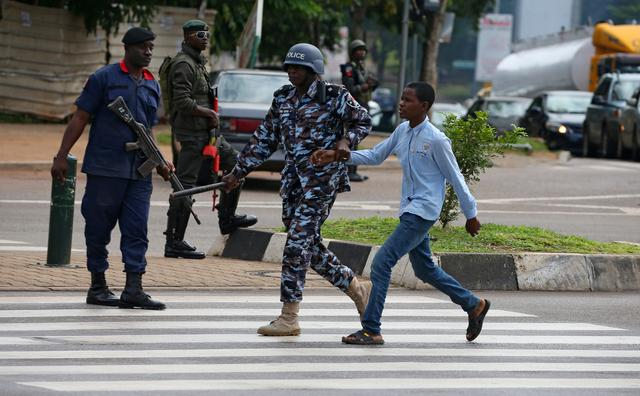 A police officer detains a young man after police dispersed members of the Islamic Movement of Nigeria (IMN) from a street in Abuja, Nigeria July 23, 2019. REUTERS/Afolabi Sotunde
