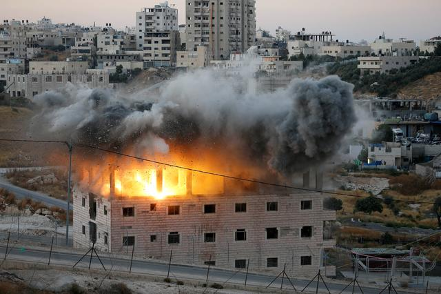 A Palestinian building is blown up by Israeli forces in the village of Sur Baher which sits on either side of the Israeli barrier in East Jerusalem and the Israeli-occupied West Bank July 22, 2019. REUTERS/Mussa Qawasma