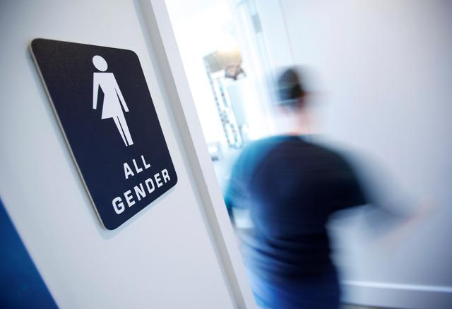 FILE PHOTO: A bathroom sign welcomes both genders in Durham, North Carolina May 3, 2016.  REUTERS/Jonathan Drake