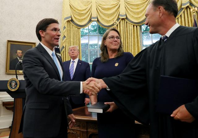 U.S. President Donald Trump looks on as Mark Esper shakes hands with Associate Justice Samuel Alito after Esper was sworn in as the new Secretary of Defense while Esper's wife Leah Esper stands nearby in the Oval Office of the White House in Washington, U.S., July 23, 2019. REUTERS/Leah Millis