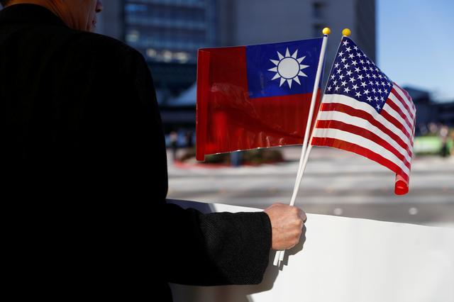 FILE PHOTO: A demonstrator holds flags of Taiwan and the United States in support of Taiwanese President Tsai Ing-wen during an stop-over after her visit to Latin America in Burlingame, California, U.S., January 14, 2017. REUTERS/Stephen Lam/File Photo