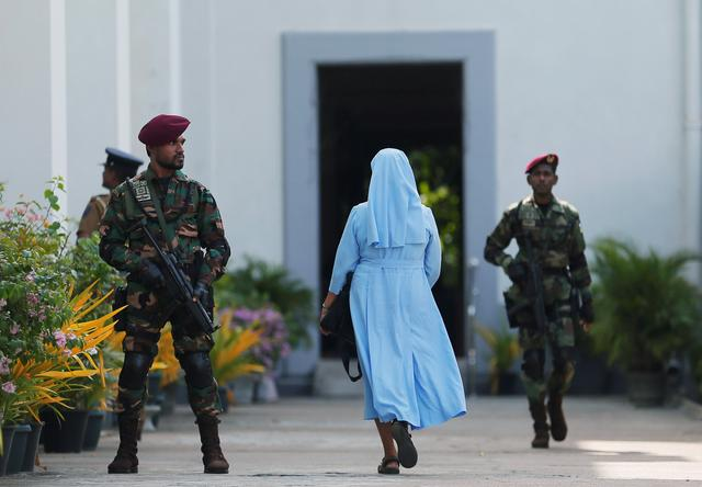 FILE PHOTO: A nun arrives as a Sri Lanka's commando soldier stands guard in front of the main entrance to St. Lucia Cathedral as survivors and families of victims of Sri Lanka's Easter Sunday bombing arrive for a special mass for those who lost their lives, in Colombo, Sri Lanka May 11, 2019. REUTERS/Dinuka Liyanawatte