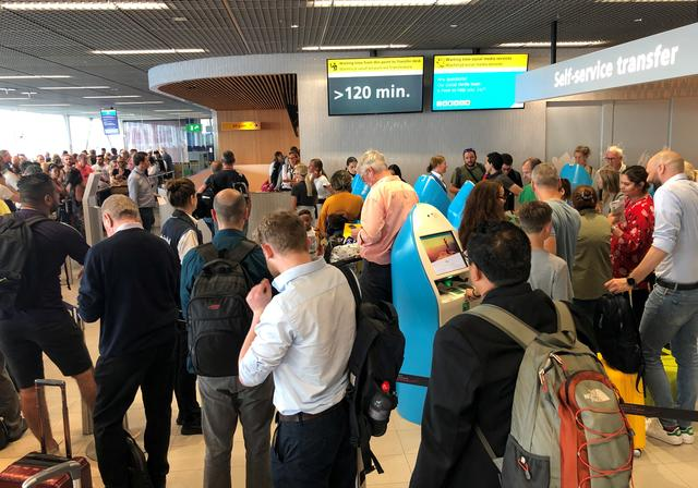 Passengers and staff wait at Amsterdam Schiphol airport during an outage at the airport's main fuel supplier that kept dozens of flights on the ground, in Amsterdam, Netherlands July 24, 2019.  REUTERS/Anthony Deutsch