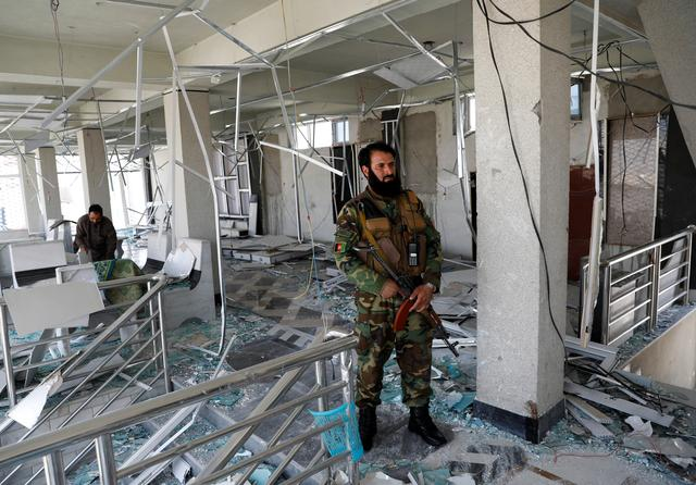 A guard of Afghan security forces inspects a damaged building at the site of a blast in Kabul, Afghanistan July 25, 2019. REUTERS/Mohammad Ismail
