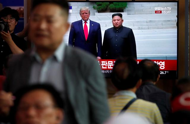 FILE PHOTO: South Korean people watch a live TV broadcast on a meeting between North Korean leader Kim Jong Un and U.S. President Donald Trump at the truce village of Panmunjom inside the demilitarised zone separating the two Koreas, in Seoul, South Korea, June 30, 2019. REUTERS/Kim Hong-Ji/File Photo