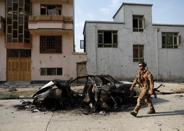An Afghan security force walks past a burnt vehicle after Sunday's attack at the site in Kabul, Afghanistan July 29, 2019. REUTERS/Mohammad Ismail