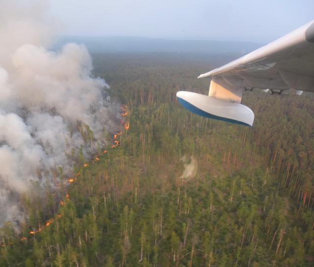 An aerial view through an aircraft window shows flame and smoke rising from a wildfire in Krasnoyarsk region, Russia in this handout picture obtained by Reuters on August 1, 2019. Russian Emergencies Ministry in Krasnoyarsk region/Handout via REUTERS