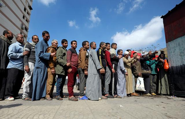 FILE PHOTO: People stand in line to cast their vote during the referendum on draft constitutional amendments, at a polling station in Cairo, Egypt April 20, 2019.    REUTERS/Stringer/File Photo