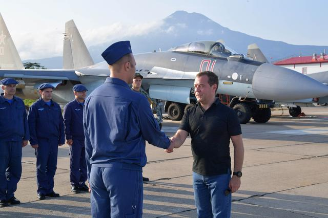 Russian Prime Minister Dmitry Medvedev shakes hands with Air Force officer at the Yasny airport during visits the Southern Kuril Island of Iturup, Russia August 2, 2019.  Sputnik/Alexander Astafyev/Pool via REUTERS