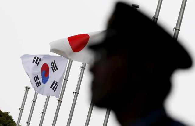 FILE PHOTO: A police officer stands guard near Japan and South Korea national flags at a hotel, where the South Korean embassy in Japan is holding the reception to mark the 50th anniversary of the normalisation of ties between Seoul and Tokyo, in Tokyo  June 22, 2015.   REUTERS/Toru Hanai/File Photo