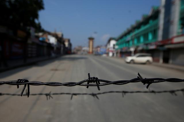 Barbed wire is seen laid on a deserted road during restrictions in Srinagar, August 5, 2019. REUTERS/Danish Ismail