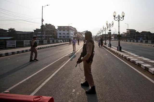 Indian security personnel stand guard on a deserted road during restrictions in Srinagar, August 5, 2019. REUTERS/Danish Ismail