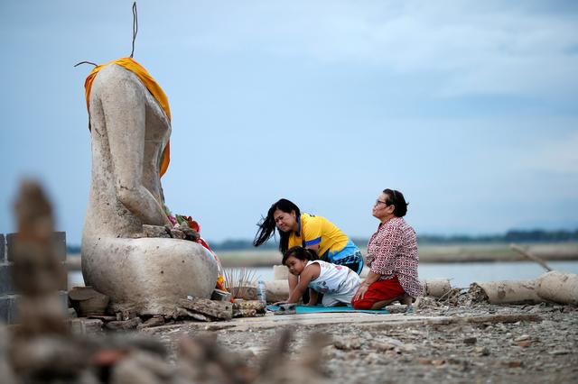 A family prays near the ruins of a headless Buddha statue, which has resurfaced in a dried-up dam due to drought, in Lopburi, Thailand August 1, 2019. Picture taken August 1, 2019. REUTERS/Soe Zeya Tun