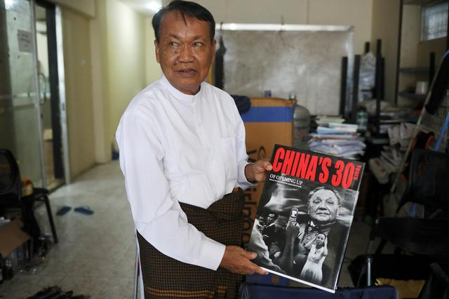 FILE PHOTO: Monywa Aung Shin, Editor-in-Chief of D. Wave Journal, the magazine distributed by National League for Democracy Party (NLD), shows one of the books he got during his trip to China in his office in Yangon, Myanmar, August 1, 2019. REUTERS/Ann Wang
