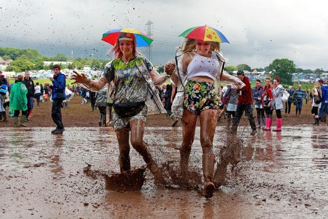 FILE PHOTO: Festival goers splash through a muddy puddle at Worthy Farm in Somerset, on the third day of the Glastonbury music festival June 27, 2014. REUTERS/Cathal McNaughton