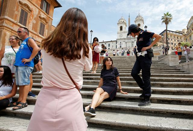 A municipal policewoman asks a tourist to rise from Rome's Spanish step, after the city's municipality banned sitting down on the famed stairs, in Rome, Italy, August 8, 2019 REUTERS/Remo Casilli